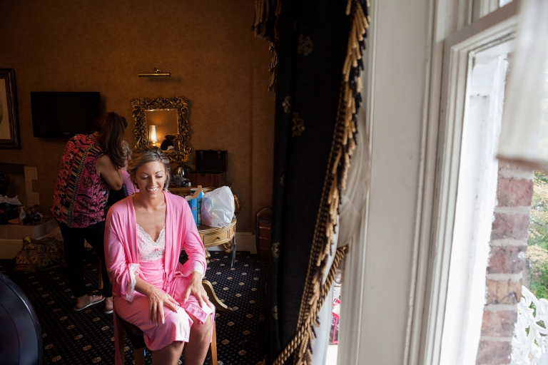 bride in sunlight from window during makeup