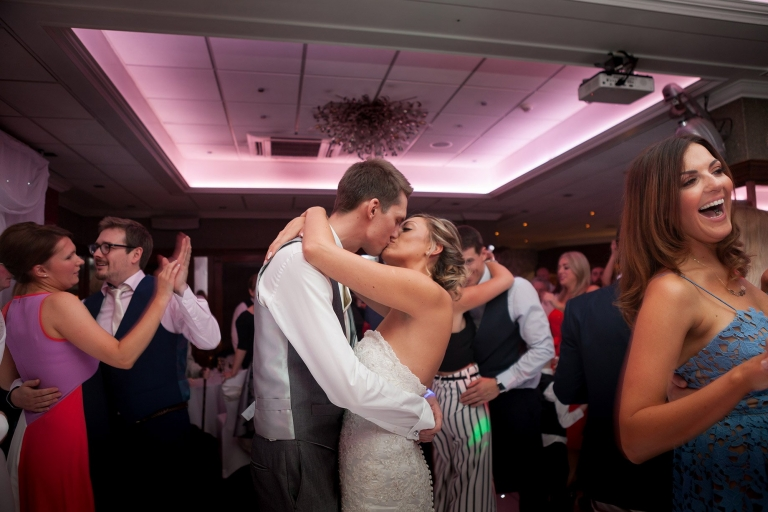 Bride and groom kissing on dance floor  at Liverpool Sefton Park Sure Hotel