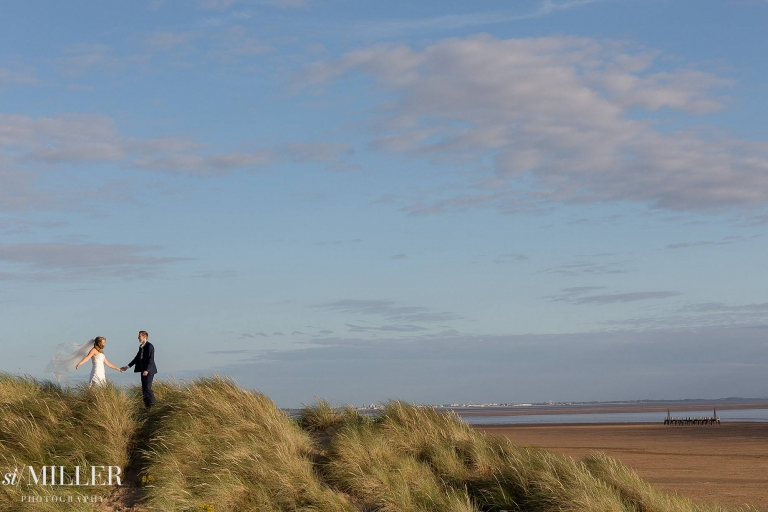 bride and groom on dunes at st. annes beech Lancashire