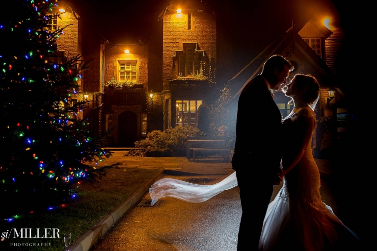 Bride and groom at night light by flash from behind with christmas tree at the villa wrea green