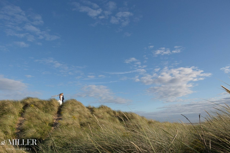 bride and groom on top of sand dunes at st annes Lancashire