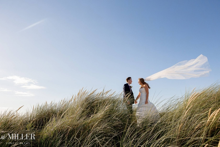 bride and groom on sand dunes at Lytham St Annes with veil blowing in the wind