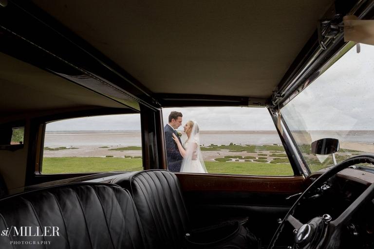 couple cuddling trough wedding car window at Lytham St Annes