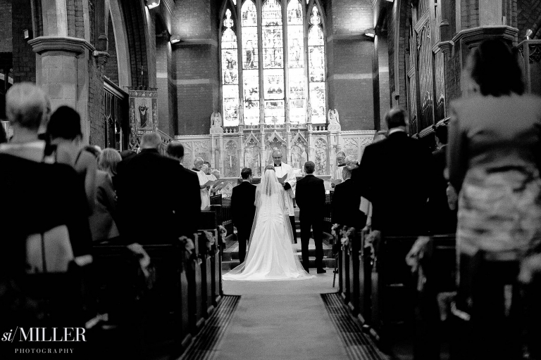 bride in the middle of the aisle at wedding ceremony at st. annes church