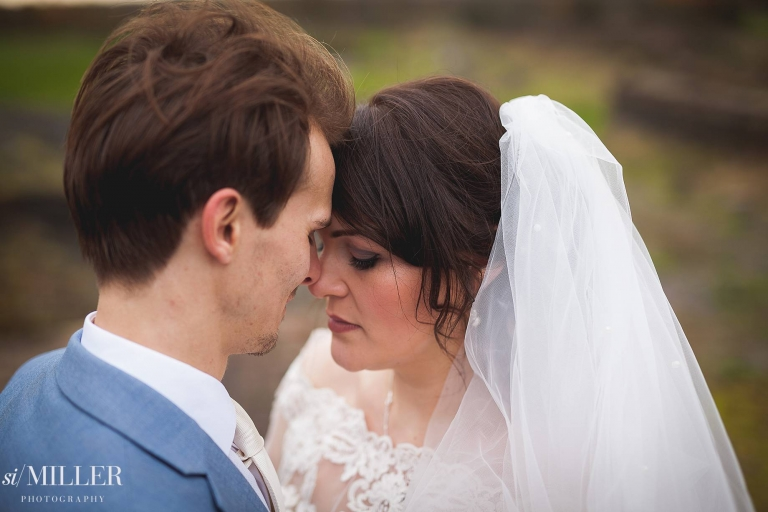 groom and bride with heads together at beeston Manor.