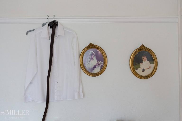 shirt hanging up next to wedding photos