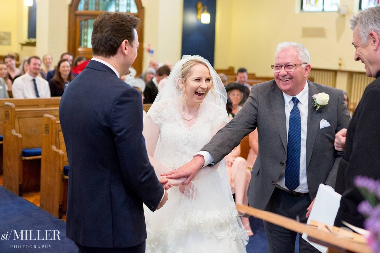 bride laughing at front of the White church St Annes as father passes hand to groom