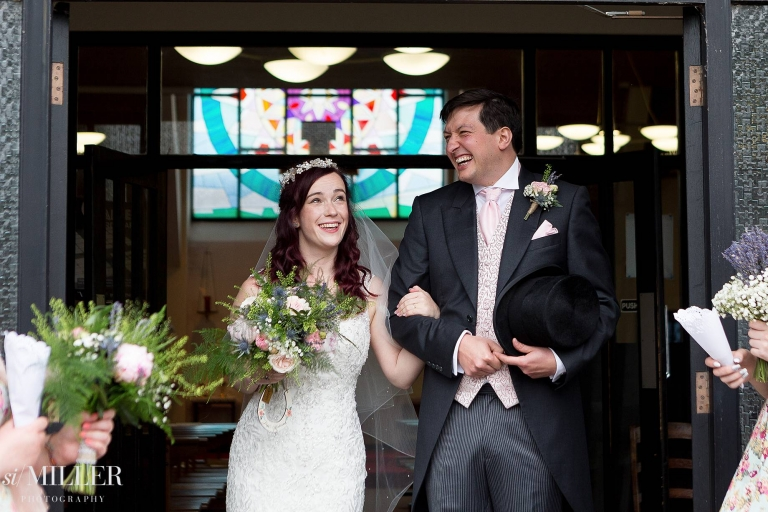 bride and groom giggling while walking out of st. Clares church Preston