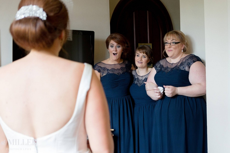 bridesmaids very happy during first look of bride in wedding dress