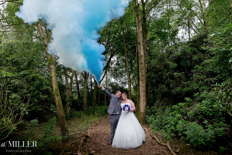 Groom holding white and blue smoke bombs, with bride at Bartle Hall Preston.