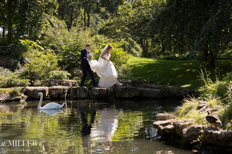 groom holding brides dress as they cross over stepping stones at Lytham St Annes.