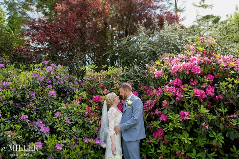bride and groom in front of pink and purple rhododendrons at Ferraris country Hotel