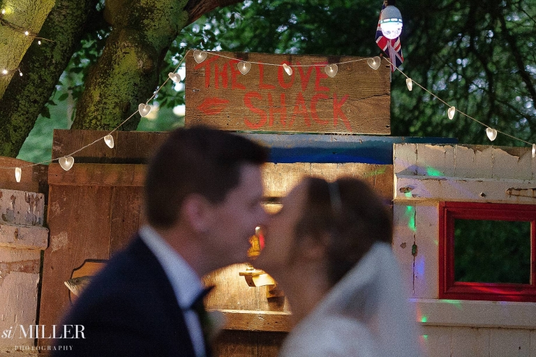 couple kissing in front of the love shack sign at spring cottage