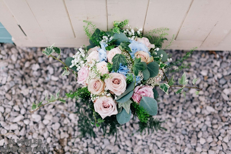 Wedding bouquet pink roses and blue carnations against wooden shed