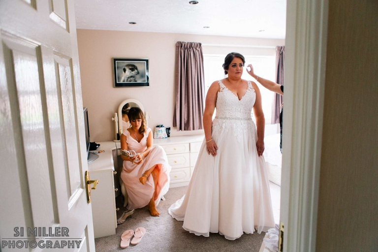 Bride and sister final finishing touches during wedding morning in Preston