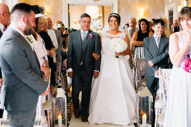 Bride smiling at groom as she walks down the aisle