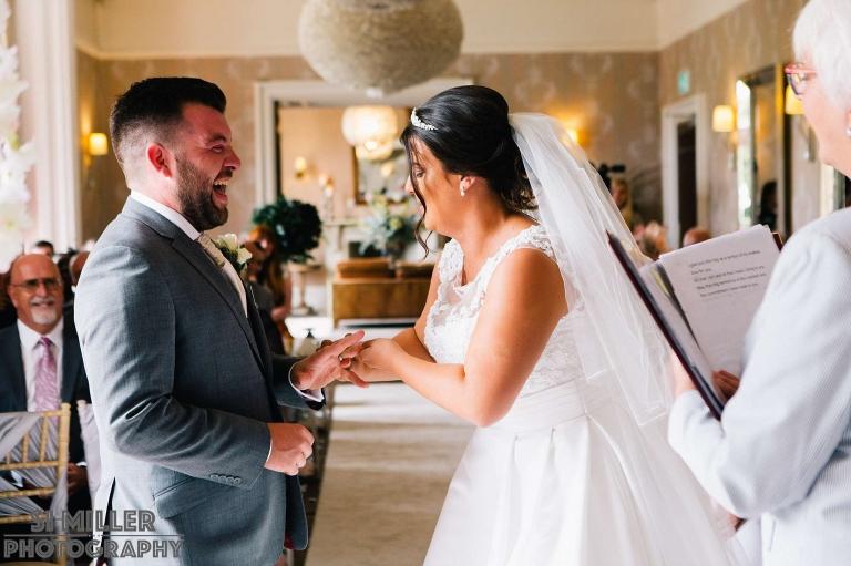bride struggling to get wedding ring on groom