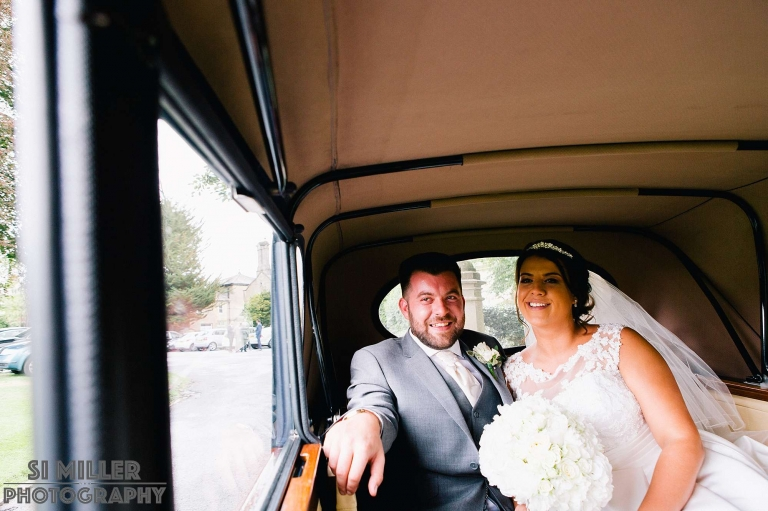Happy couple in wedding car going for a little spin.