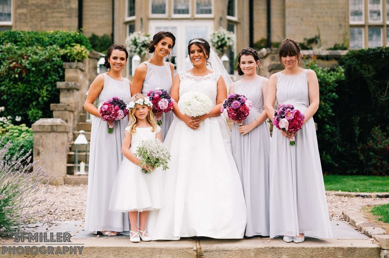 natural portrait of bridesmaids and bride on the steps of Falcon Manor