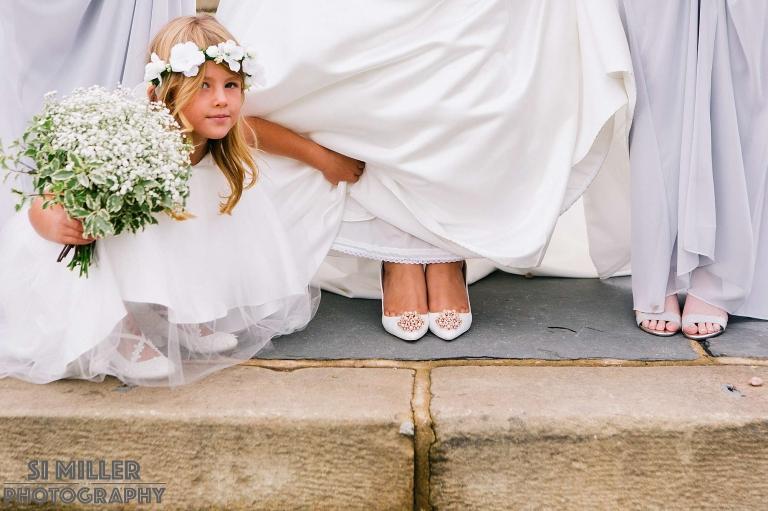 Flower girl peeking at brides shoes