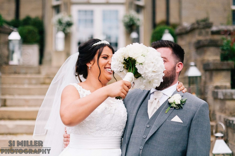 bride pushing her bouquet into grooms face