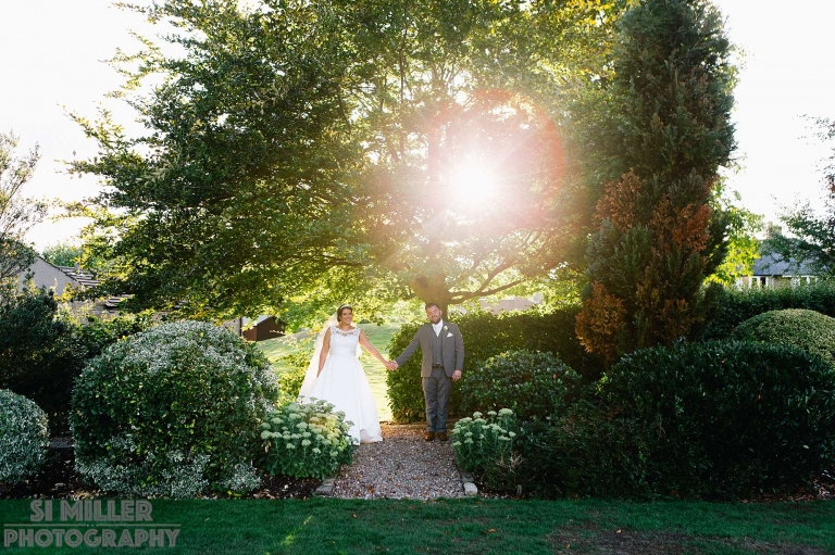 Newly weds portrait hand in hand with tree and lens flare