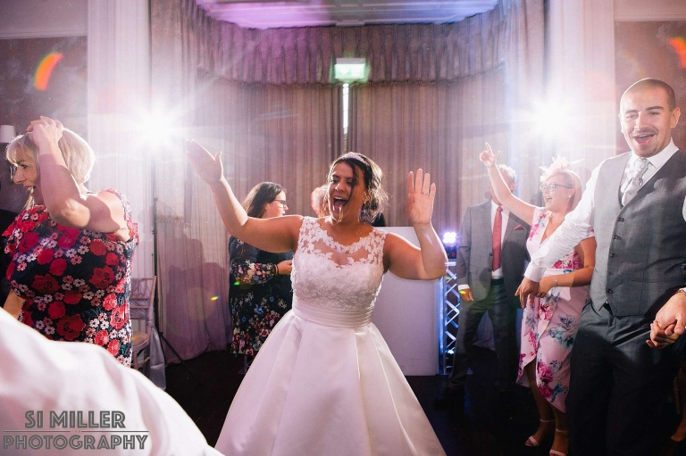 bride with hands in the air during evening do