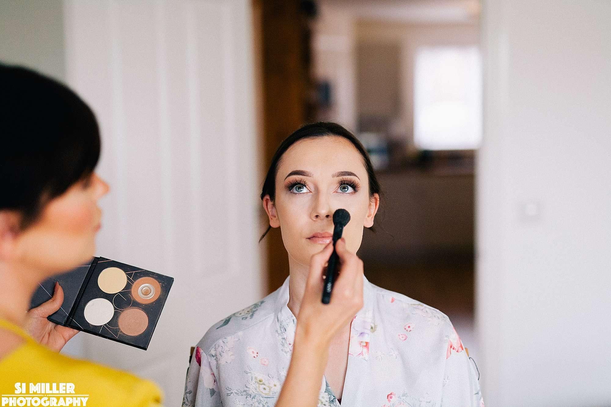 Makeup artist doing make up on bride