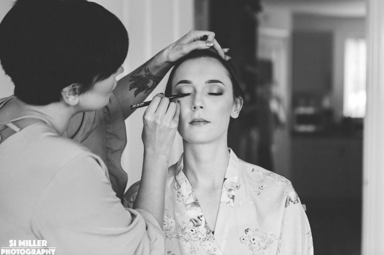 Makeup artist putting eyeliner on bride