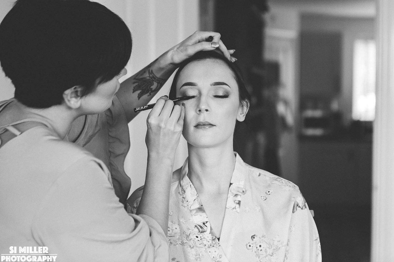 Makeup artist putting eyeliner on bride