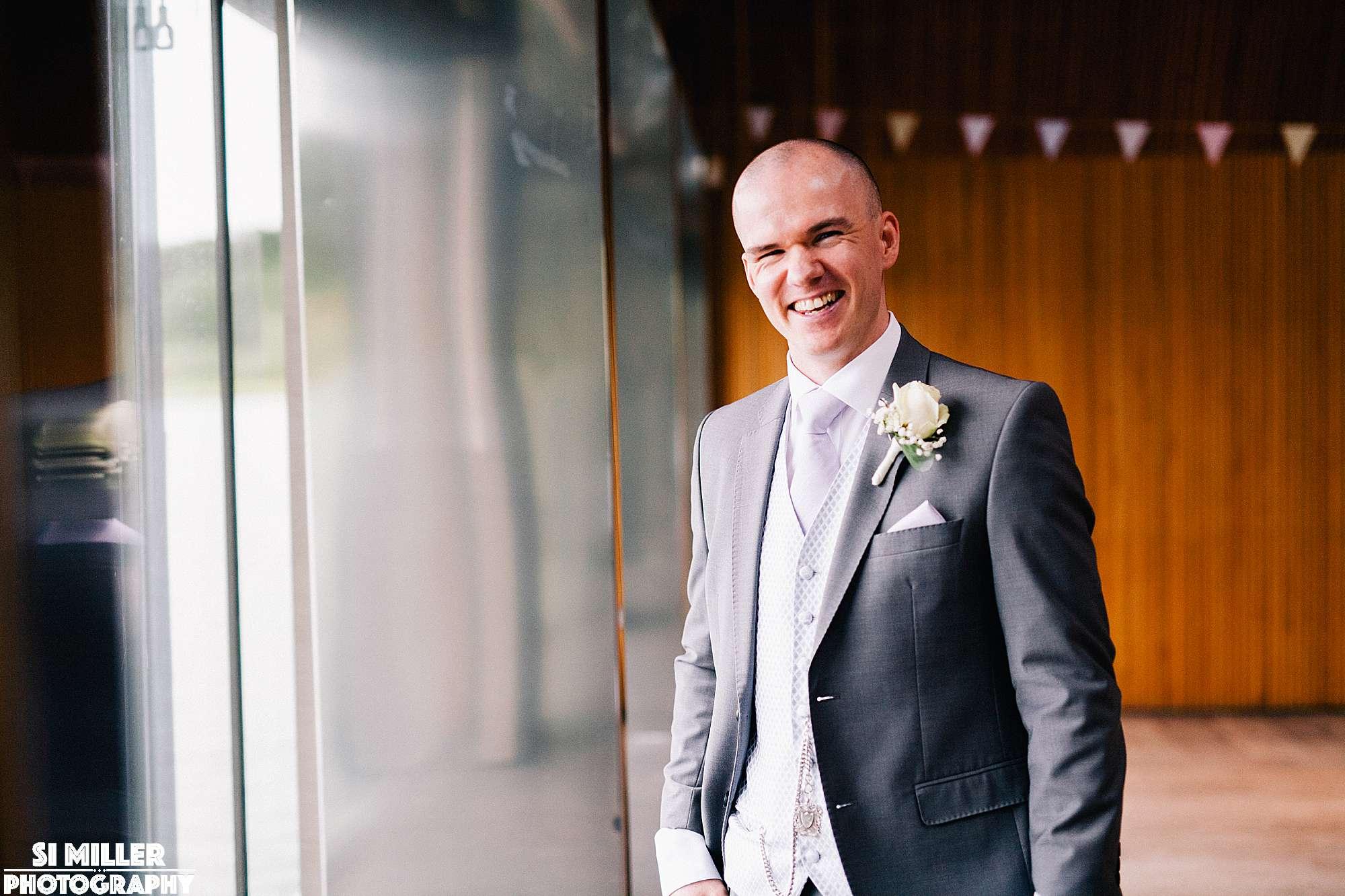 groom laughing by window in the meadow lake suite brockholes
