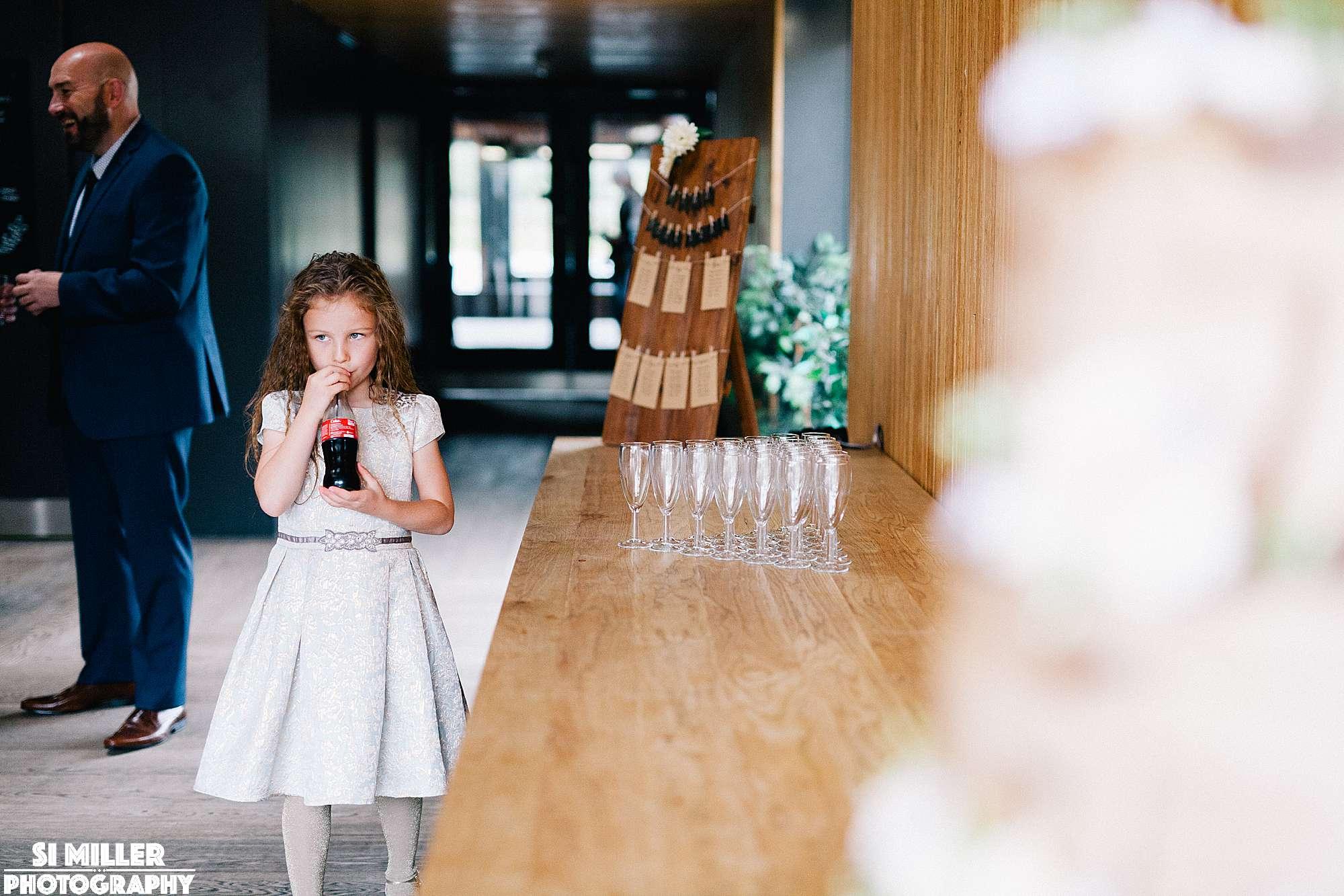 flower girl drinking coca cola bottle at wedding