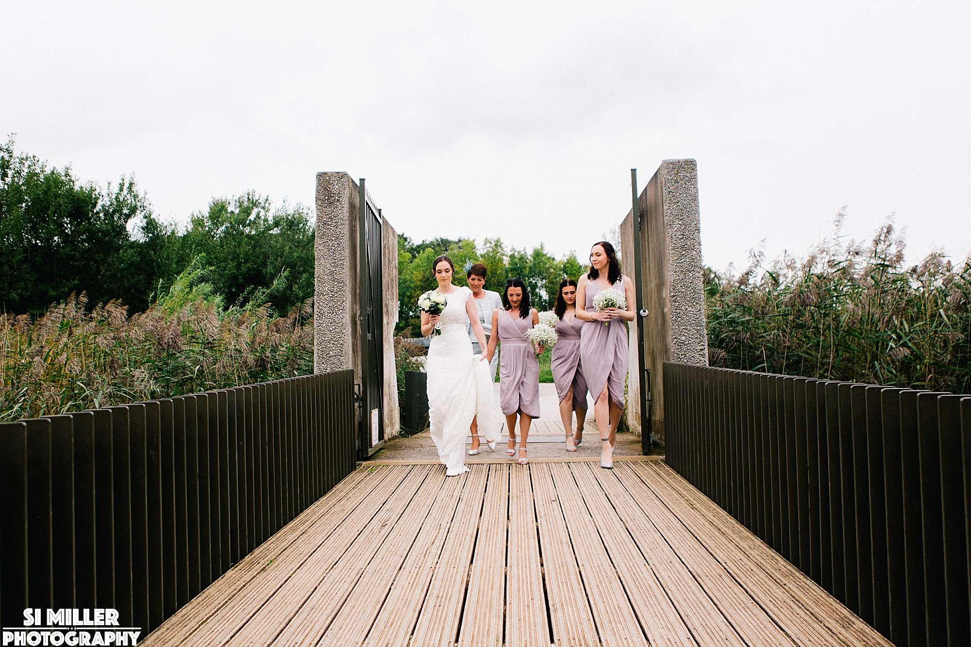 bride and bridesmaids walking over bridge to brockholes wedding