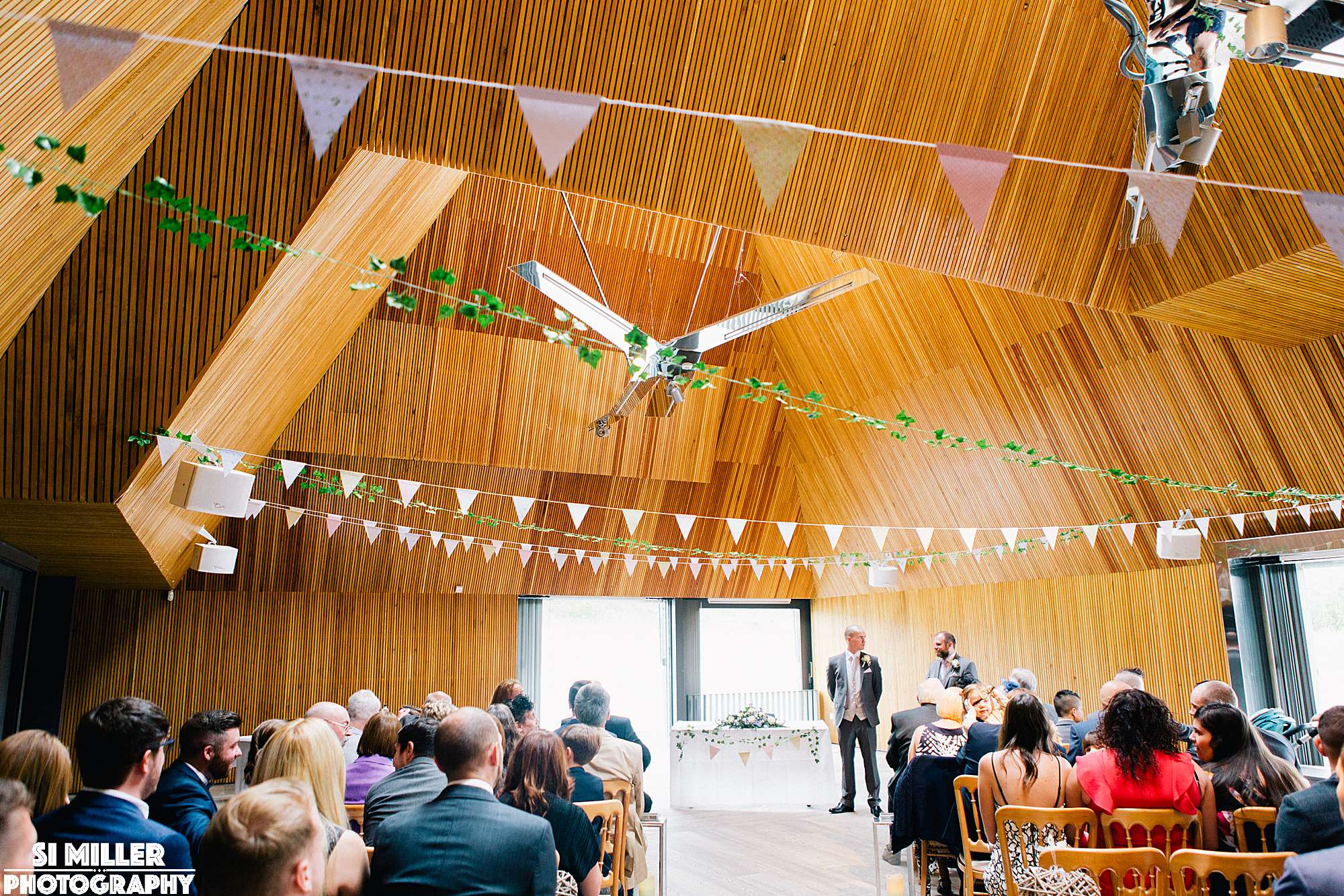 groom waiting for brides entrance below bunting at brockholes wedding ceremony