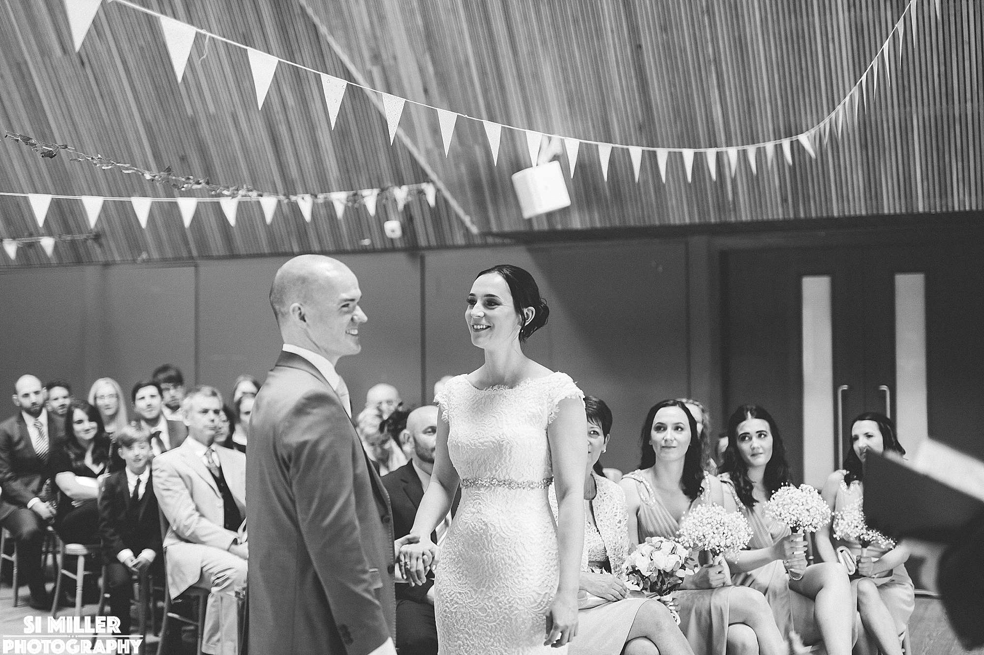 Couple holding hands whilst saying wedding vows at brockholes