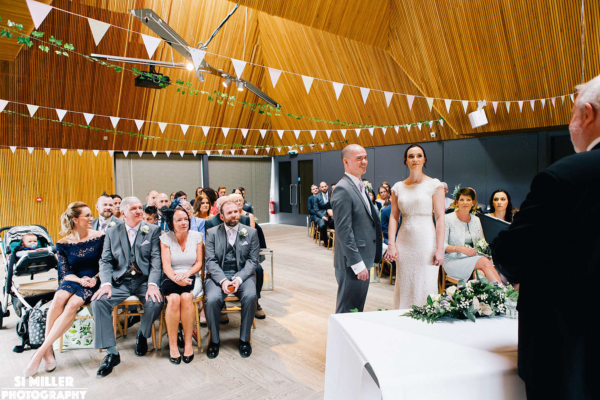 Wedding guests looking at couple during wedding ceremony at brockholes
