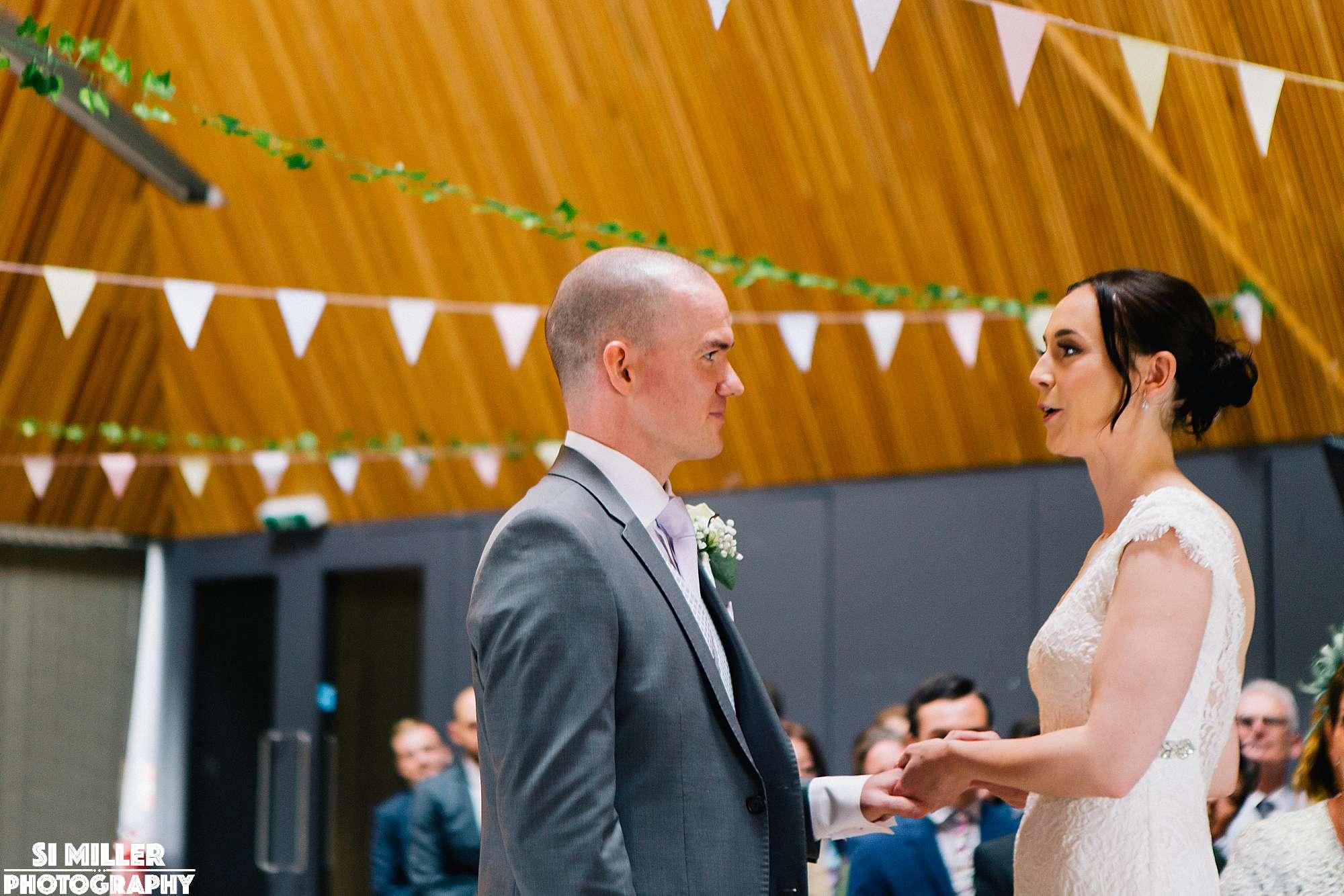 Bride placing ring on grooms hand at brockholes Preston