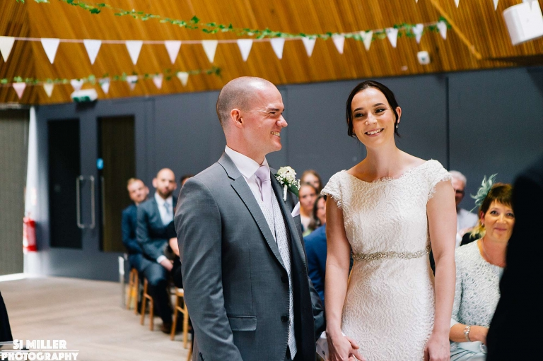 Bride and groom smiling during wedding ceremony at brockholes