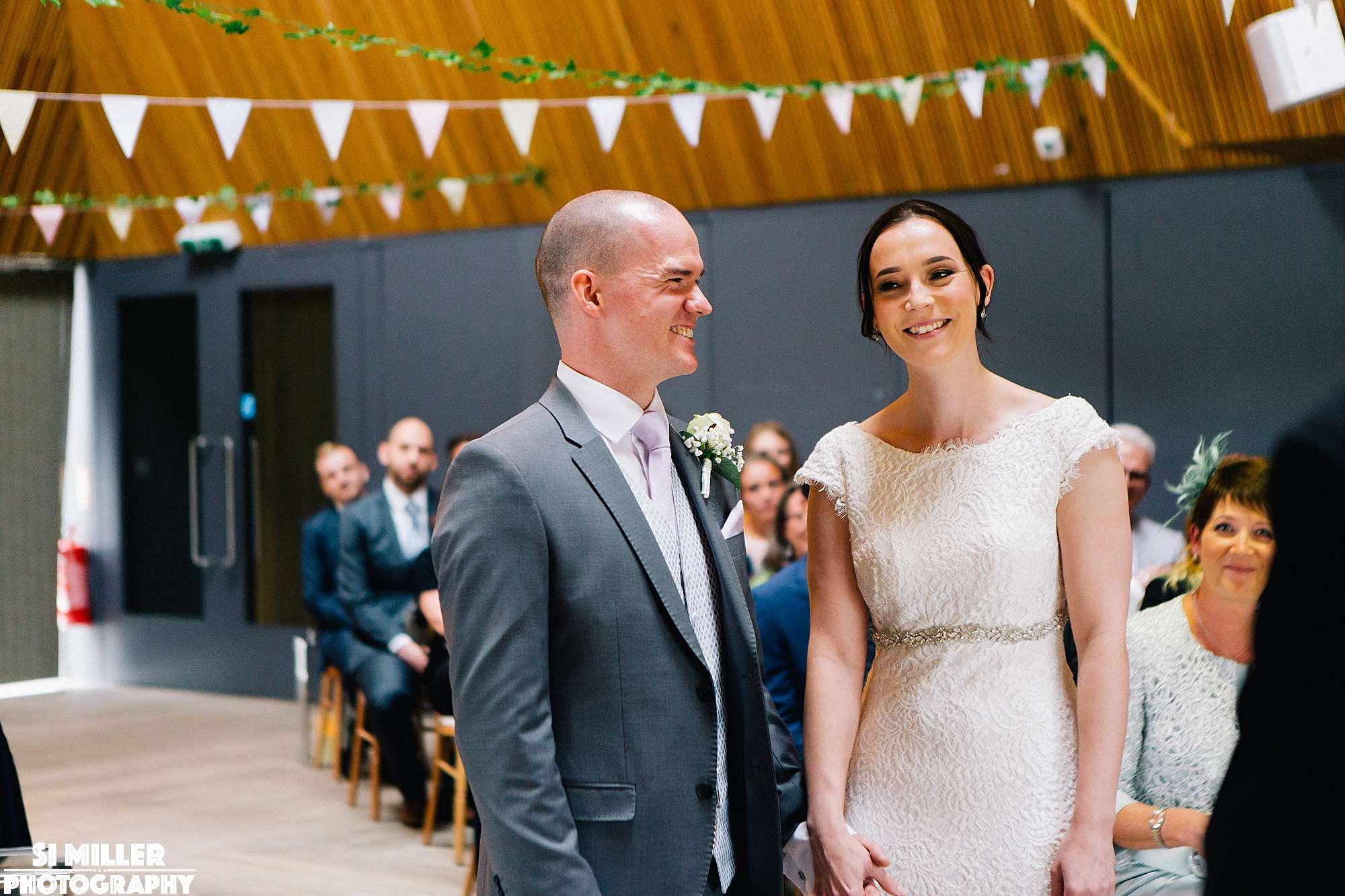 Bride and groom smiling during wedding ceremony at brockholes