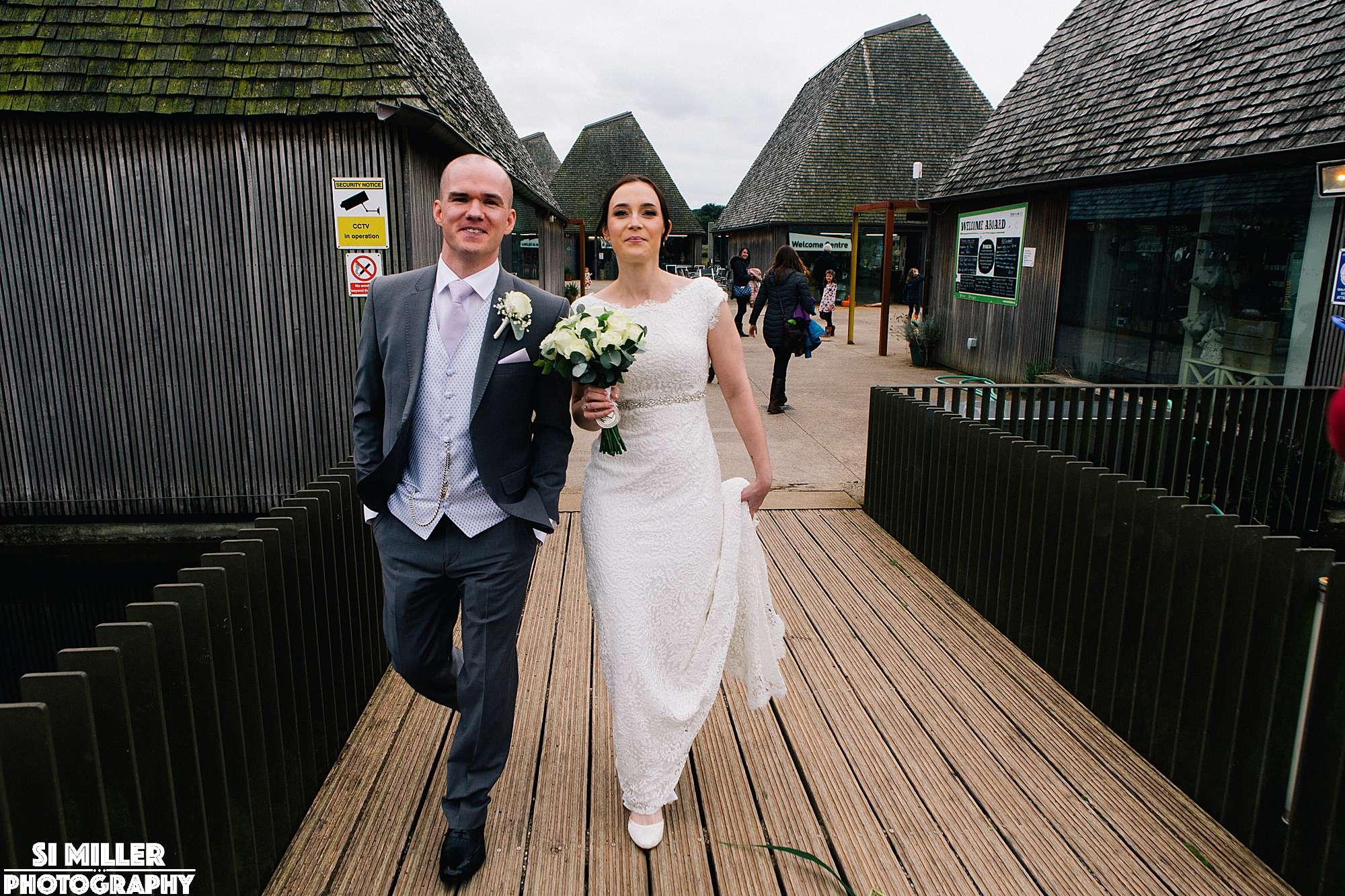 Bride and groom walking across bridge on brockholes visitor island