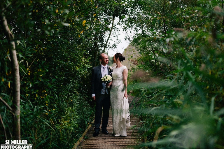 Bride and groom on path between reed bed at brockholes