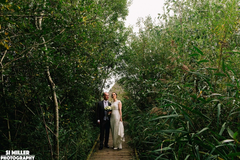 Wedding portrait of couple in between reed beds at brockhalls