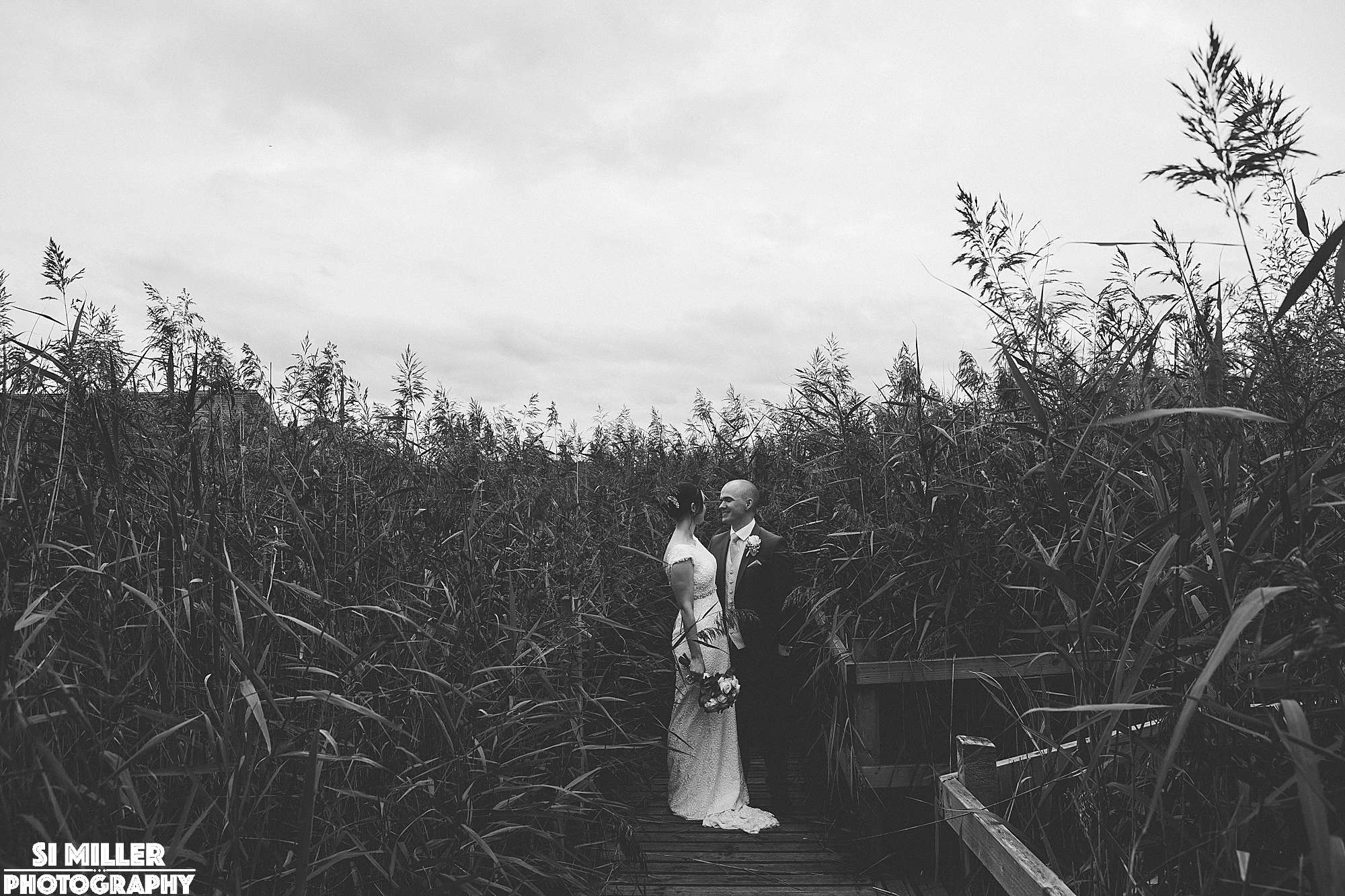 Black and white photo of couple with reeds behind them at brockholes