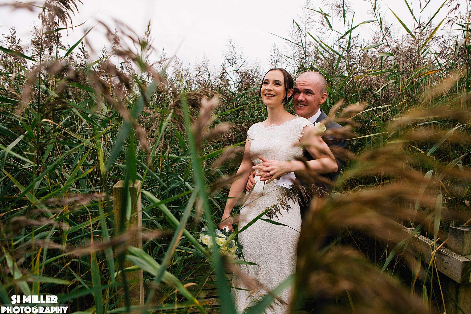 Groom hugging bride surrounded by reeds at brockholes