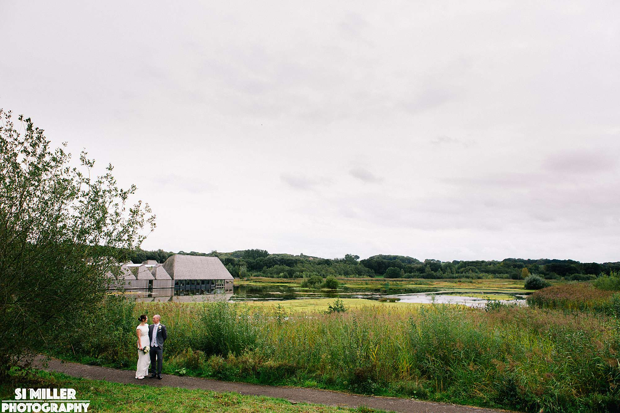 Wedding couple with brockholes visitor centre and lake