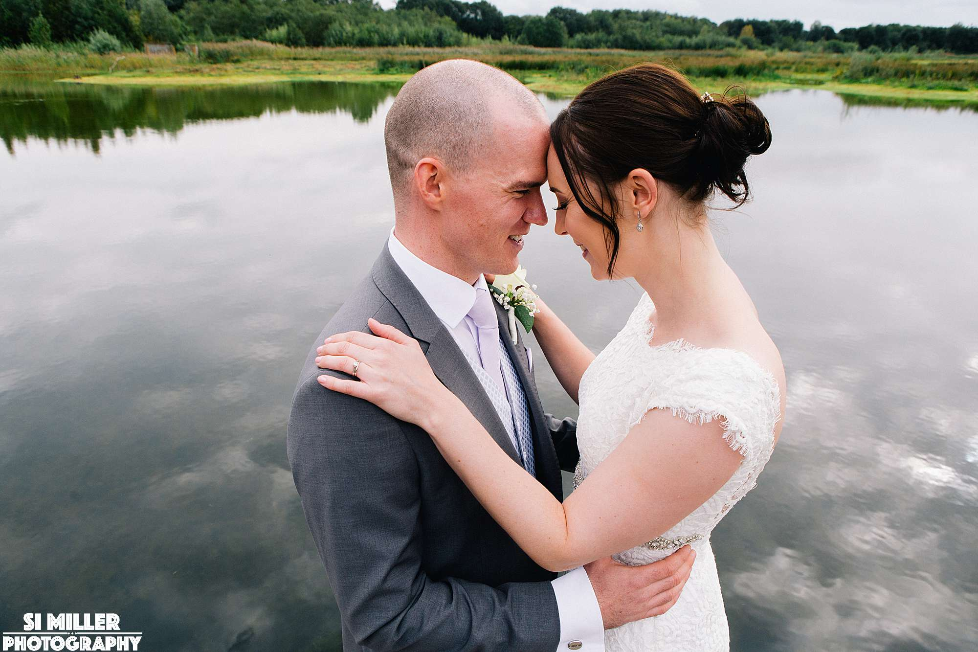 Wedding couple cuddling with heads together And lake behind them at brockholes
