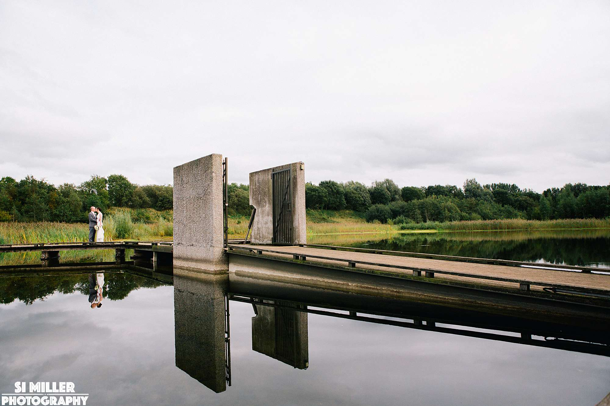 Newly weds with reflection of them and floating island at brockholes nature reserve