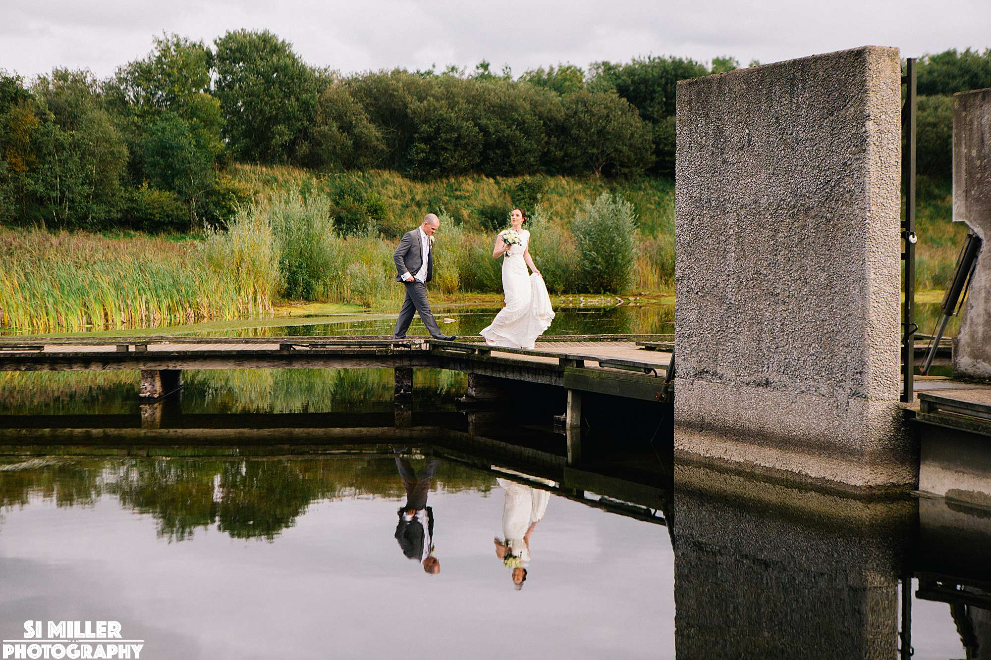 Bride and groom walking on jetty to brockholes floating island at brockholes nature reserve