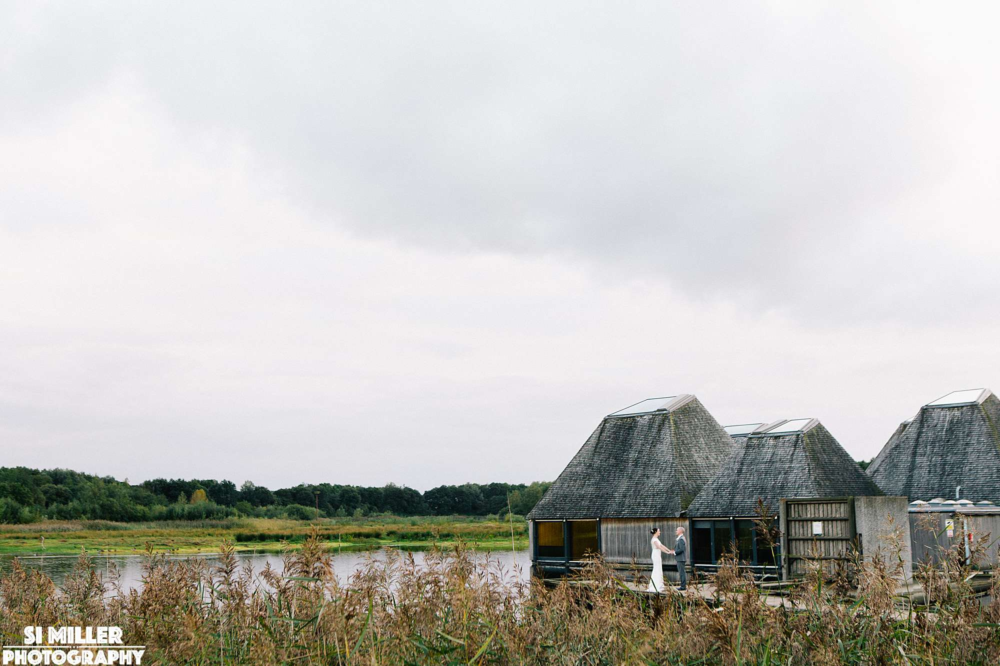 Wedding couple cuddling on jetty with brockholes vistor centre and lake behind them