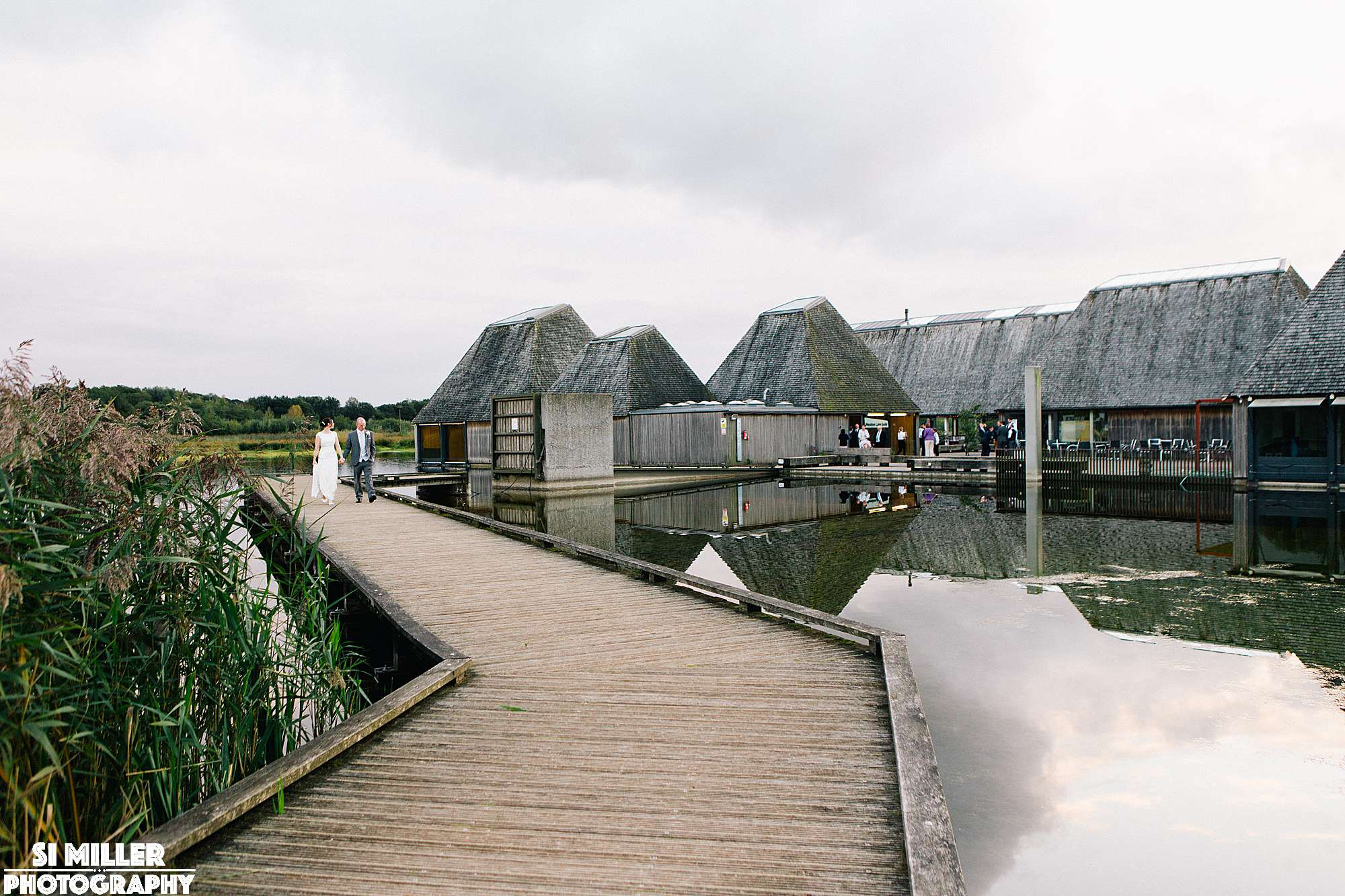 Wedding couple walking on jetty away from brockholes visitor island